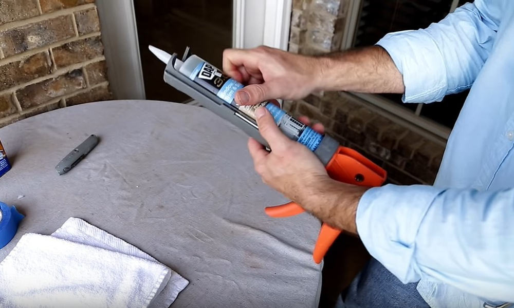 Place the caulk tube in the caulk gun