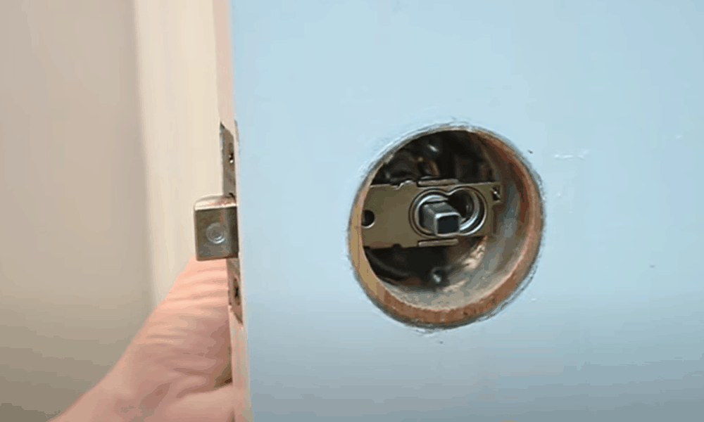 Insert one half of the doorknob in through the latch