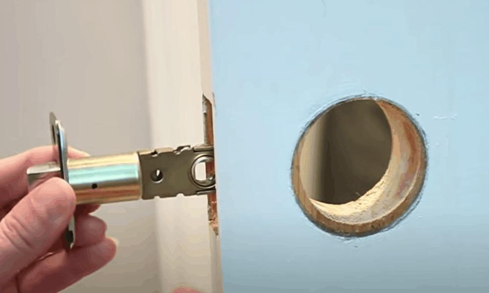 Insert the latch through the edge of the door
