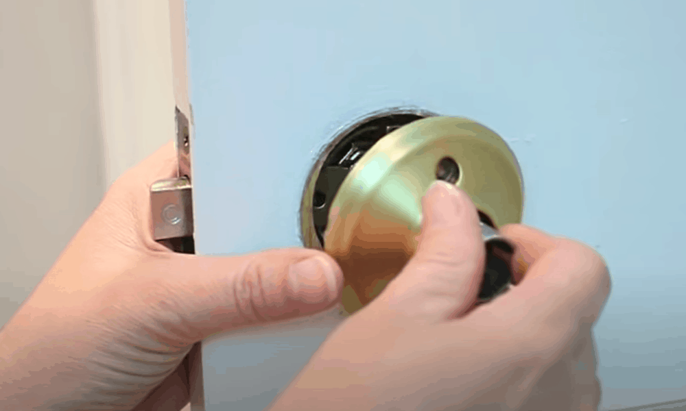 Insert the other half of the doorknob in through the other side of the latch